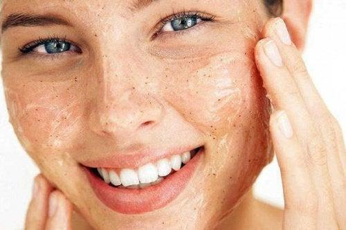 kobieta robiąca peeling twarzy zmniejszy Wpływ menopauzy na skórę