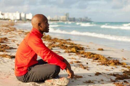 Mężczyzna siedzący na brzegu morza