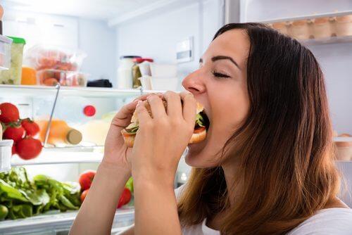 Głód psychiczny - kobieta jedząca hamburgera