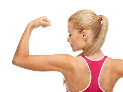 Kobieta napina mięśnie ramion