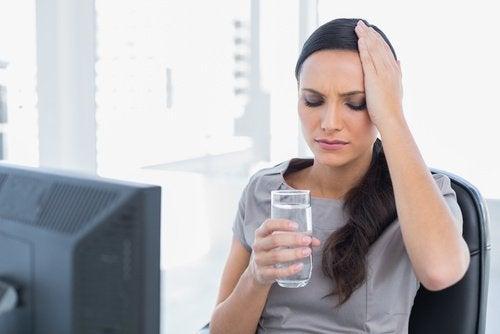 Kobieta z gólem głowy i szklanką wody