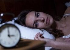 kobieta w łóżku i budzik