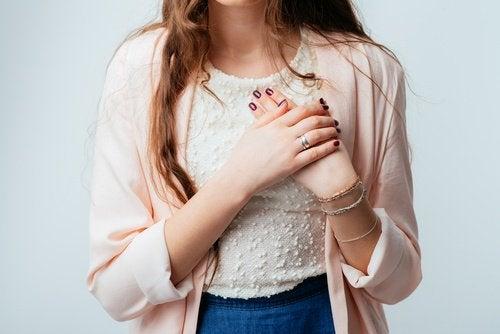 Kobieta trzyma dłoń na sercu. Jagody wpływają korzystnie na układ wieńcowy