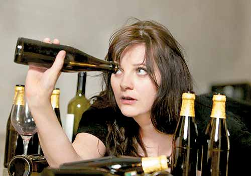 Dziewczyna zagląda do butelki - alkoholizm
