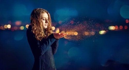 Kobieta zdmuchuje pyłek z dłoni