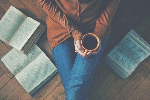 Kobieta pije herbatę i czyta książki