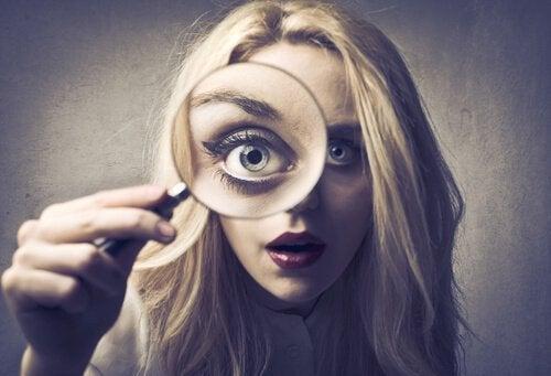 Kobieta patrzy przez lupę, czyli sposób myślenia perfekcjonisty