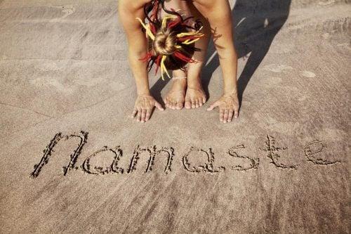 Kobieta uprawia jogę na plaży - namaste