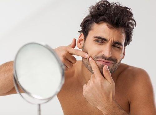 Mężczyzna wyciskający wyprysk przed lustrem
