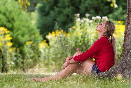 Kobieta odpoczywa pod drzewem na łące dobry sen świeże powietrze
