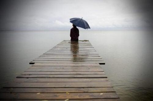 Człowiek siedzi na molo w deszczu - samotność
