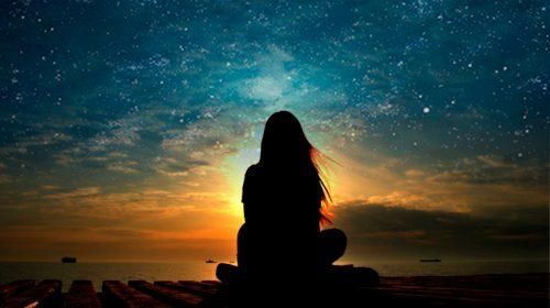 Kobieta medytuje o zachodzie słońca