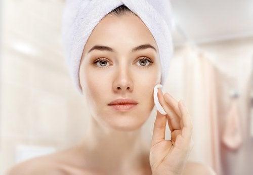 Kobieta przed lustrem oczyszcza twarz