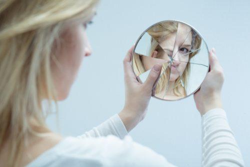 Kobieta patrzy w potłuczone lustro
