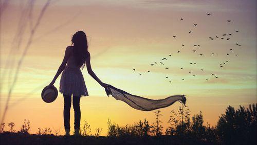 Kobieta spaceruje po łące o zachodzie słońca