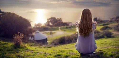 Kobieta siedzi na łące - świadome izolowanie się