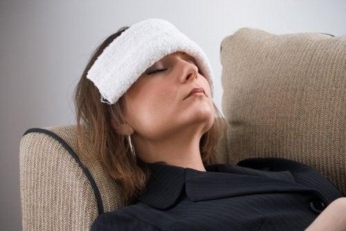 Kobieta leży z kompresem na głowie