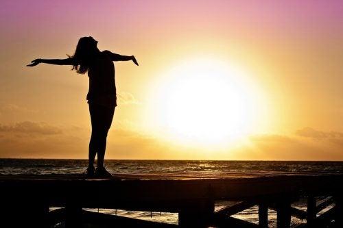 Kobieta otwiera ramiona o zachodzie słońca