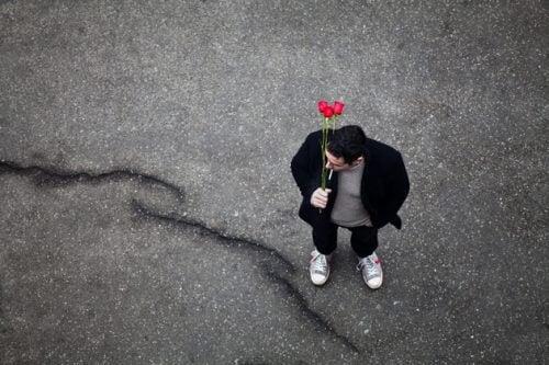 Mężczyzna czeka na ulicy z kwiatami
