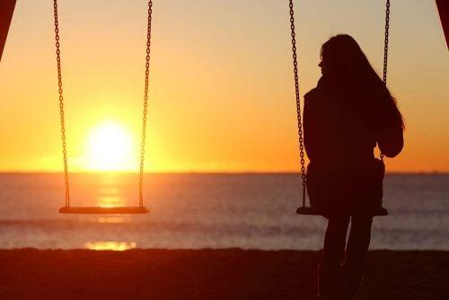 Kobieta siedzi na huśtawce - samotność