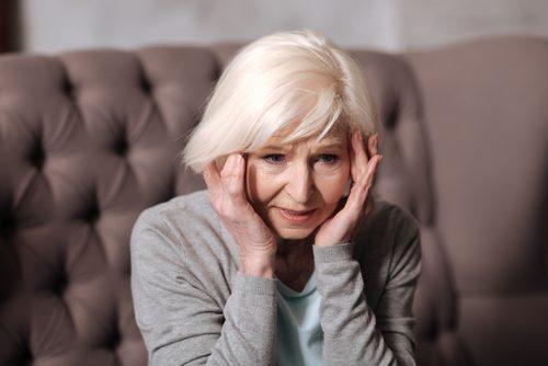Starsza kobieta trzyma się za głowę - choroby neurodegeneracyjne