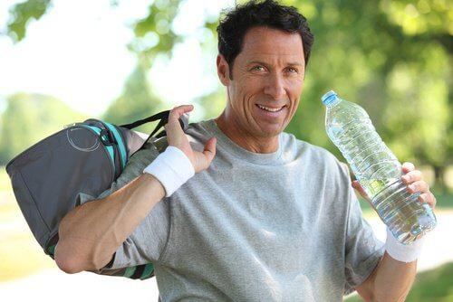 Trenujący mężczyzna nawadnia się wodą
