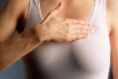 Kobieta z dłonią na klatce piersiowej
