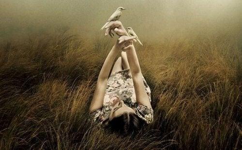 Kobieta leży na łące i trzyma w dłoni ptaki