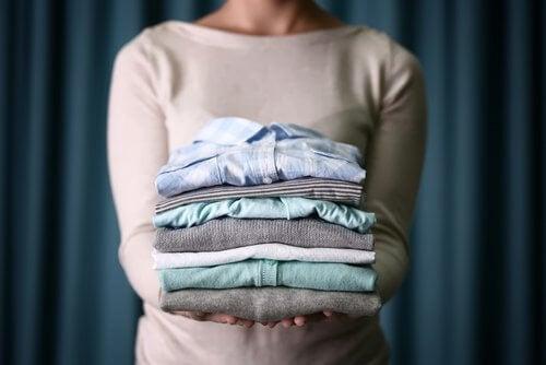 Kobieta trzyma poskładane ubrania
