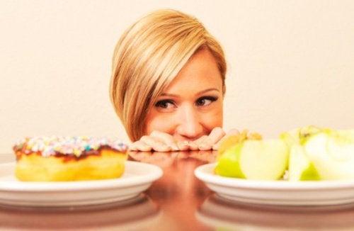 Kobieta obserwuje ciastka, stres może wywoływać wzmożony apetyt
