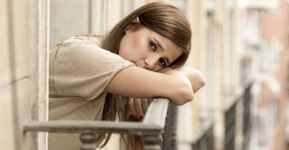 Smutna kobieta stoi na balkonie - stany lękowe