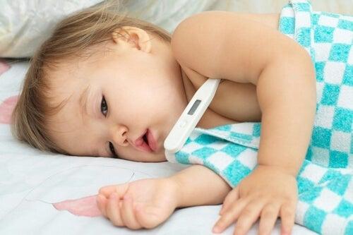 Małe dziecko z termometrem a Wirus Coxackie