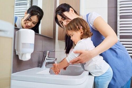 Mama myje córce ręce a Wirus Coxackie
