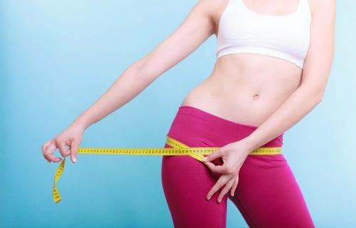 Kobieta mierzy obwód bioder - odchudzanie