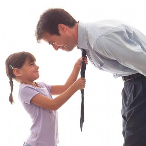 Ojciec uczy córkę wiązać krawat