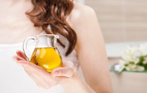 Oliwa z oliwek z pierwszego tłoczenia trzymana przez kobietę