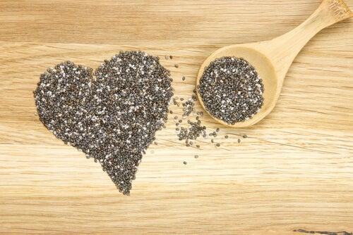 zdrowe nasiona chia ułożone w kształcie serca z drewnianą łyżką