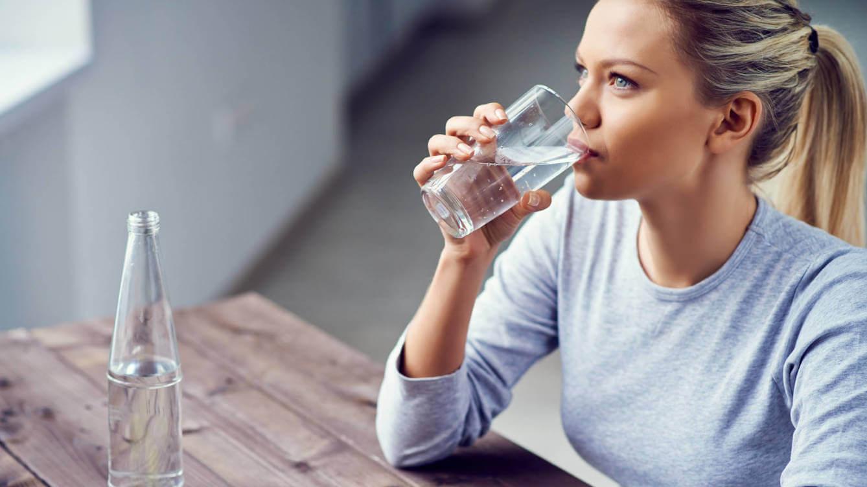 Kobieta pijąca wodę na lepsze krążenie krwi w nogach