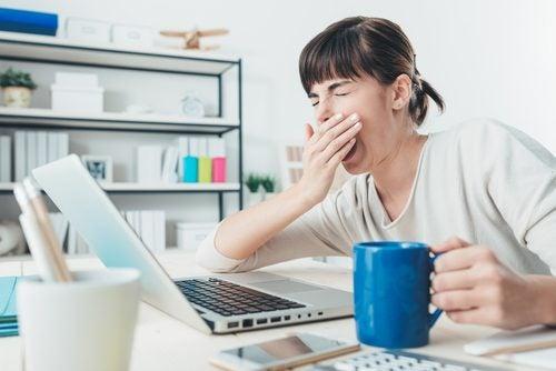 zmęczenie nadnerczy a chroniczne zmęczenie - ziewająca kobieta z kubkiem kawy i komputerem