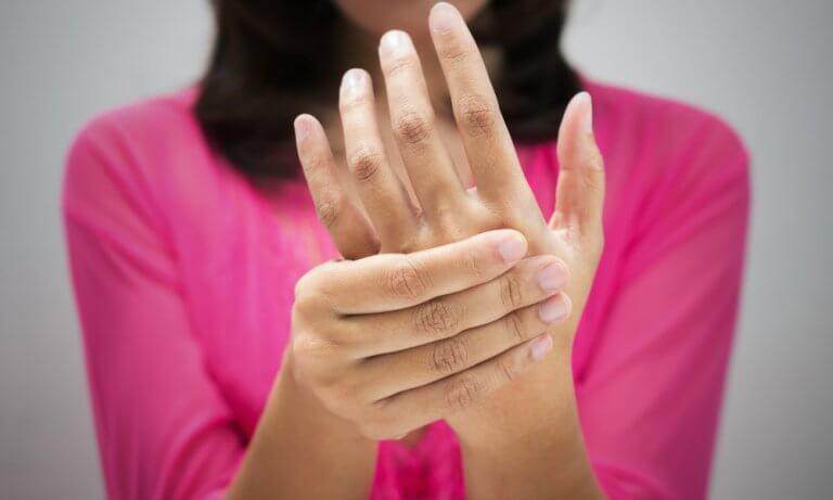 Kobieta przyma swoją dłoń
