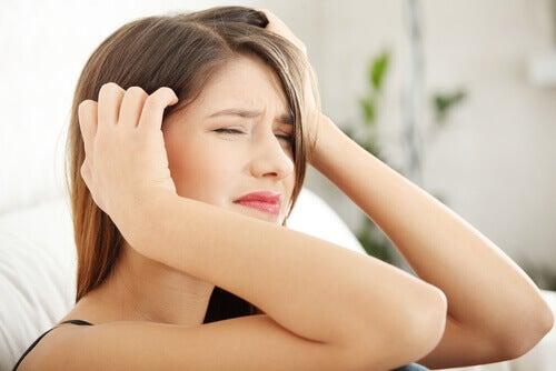 Kobieta z silnym bólem głowy spowodowanym przez stres
