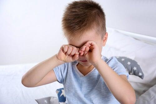 Chłopiec przecierający oczy chory na zespół aspergera