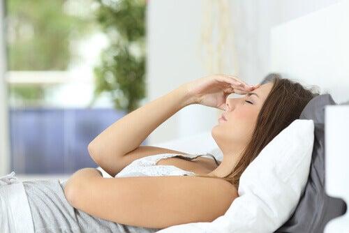 Kobieta z bólem głowy leży w łóżku