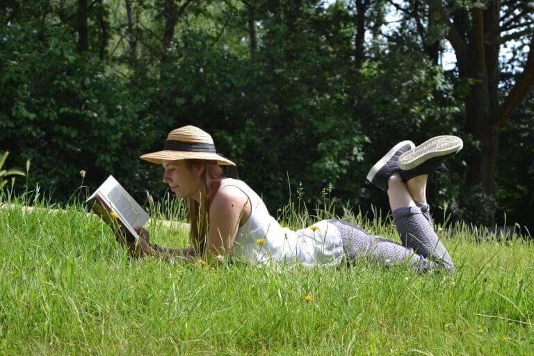 Kobieta czyta książkę na łące
