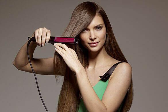 Dziewczyna prostująca włosy. prostownica zamiast zelazka . plamy na ubraniach