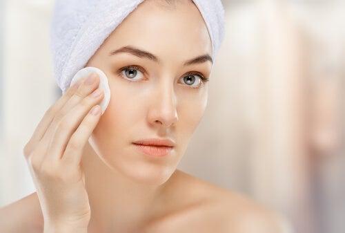 Kobieta oczyszcza skórę wacikiem