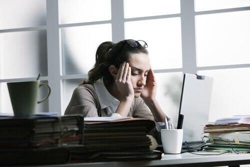 Kobieta w biurze cierpi na ból głowy spowodowany przes stres