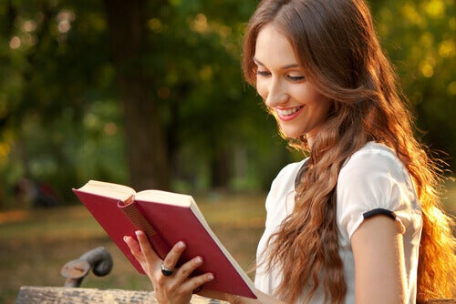 Kobieta sama w parku czyta książkę