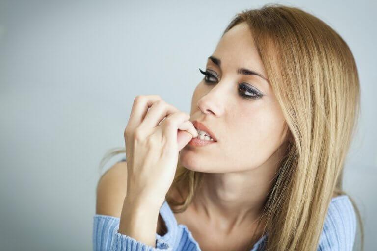 Kobieta obgryza paznokcie