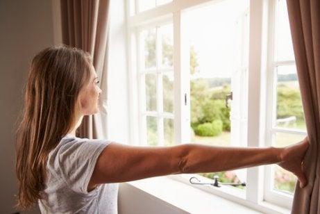 Kobieta odsłaniająca okno